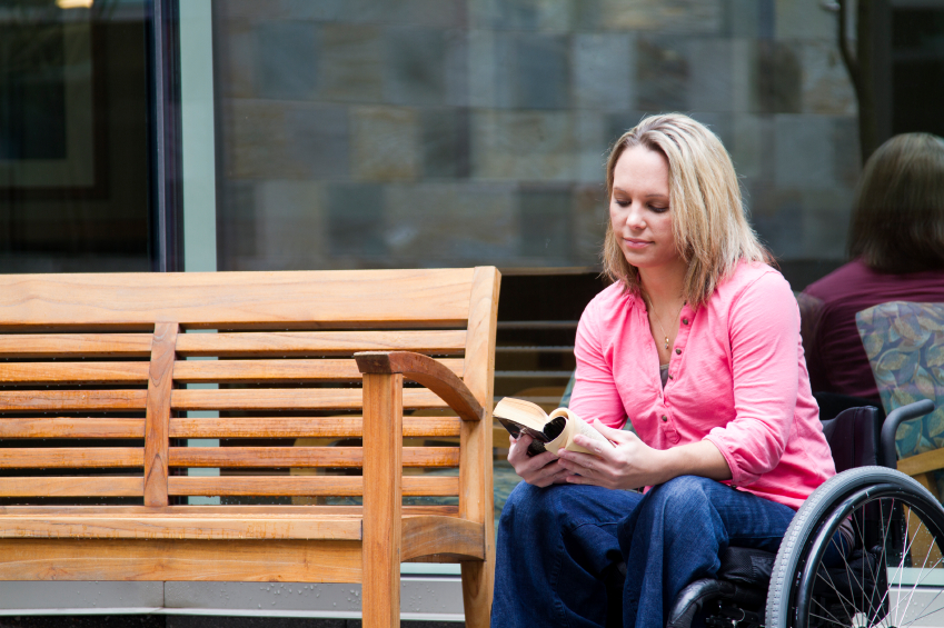 woman sitting near bench in wheelchair